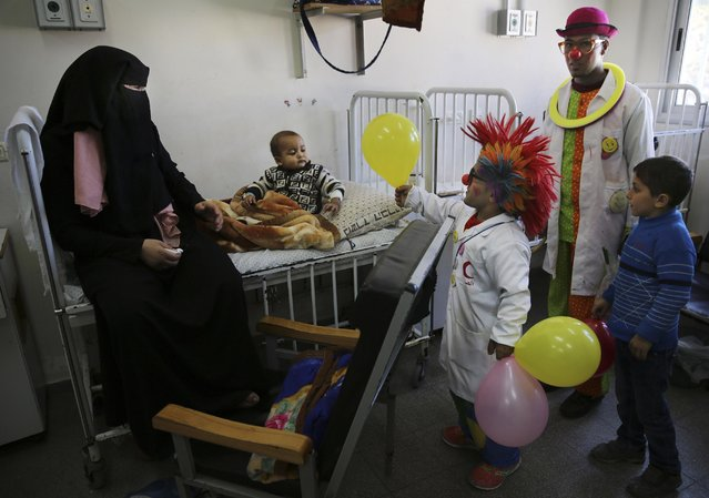 In this Thursday, March 17, 2016 photo, Palestinian clown doctor Alaa Miqdad, center, gives 3-year-old Abdallah Saleem a balloon, in the department of kidney diseases at Al-Rantisi children's hospital in Gaza City. (Photo by Adel Hana/AP Photo)