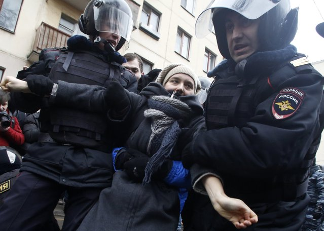 Russian police officers detain an opposition activist outside a court room in Moscow, Russia, Monday, February 24, 2014, where hearings started against opposition activists detained on May 6, 2012 during a rally at Bolotnaya Square. (Photo by Denis Tyrin/AP Photo)
