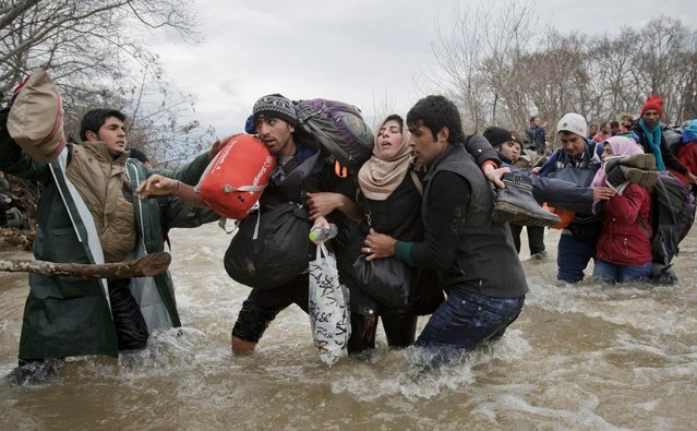 A handout photo made available by the World Press Photo (WPP) organization on 13 February 2017 shows a picture by The Associated Press photographer Vadim Ghirda that won the Contemporary Issues – Second Prize, Singles award of the 60th annual World Press Photo Contest, it was announced by the WPP Foundation in Amsterdam, The Netherlands on 13 February 2017. Caption: A woman is supported by two men while crossing a river, as refugees attempt to reach Macedonia on a route that would bypass the border fence, on 14 March 2016. Hundreds of refugees walked out of an overcrowded camp on the Greek-Macedonian border on this day, shortly after the closure of Macedonia's borders, determined to head north despite the dangers of the crossing. (Photo by Vadim Ghirda/EPA/World Press Photo)
