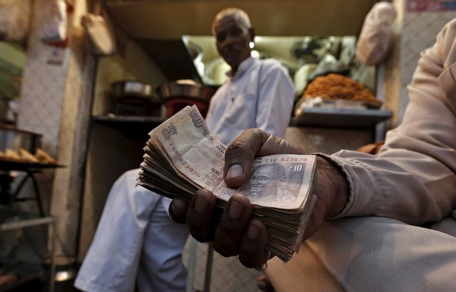 A street side restaurant owner holds a bundle of Indian currency notes as he sits outside his restaurant in New Delhi in this November 22, 2013 file photo. Thousands of garment, leather, handicraft, and gems and jewellery exporters have watched helplessly as the rupee has appreciated by a quarter against Europe's common currency over the past 12 months. (Photo by Adnan Abidi/Reuters)