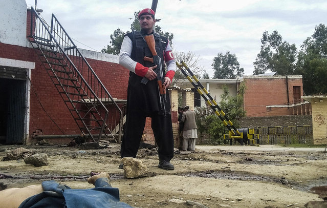 A Pakistani security officer stands alert at the site of a bombing in Ghalanai in the Pakistan's tribal region of Mohmand, Wednesday, February 15, 2017. A Taliban suicide bombing targeted the administrative headquarters of a tribal region in northwestern Pakistan on Wednesday, killing scores of policemen and two passers-by, according to officials. (Photo by Alamgir Khan/AP Photo)
