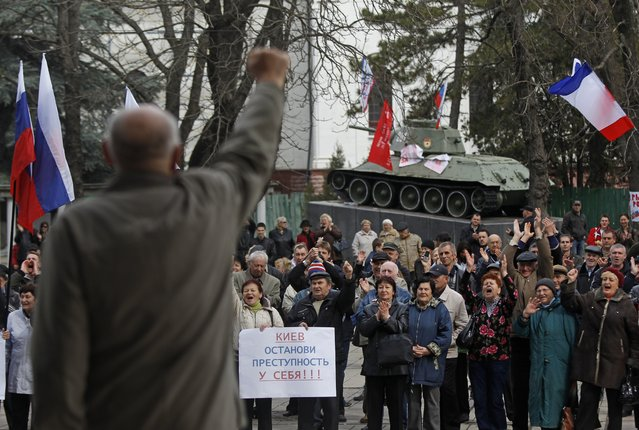 """Pro-Russia demonstrators rally at the local parliament building, with a monument of World War II in the background, in Crimea's capital Simferopol, Ukraine, Thursday, March 6, 2014. A poster reads """"Kiev, Stop Crime at Home"""". (Photo by Sergei Grits/AP Photo)"""