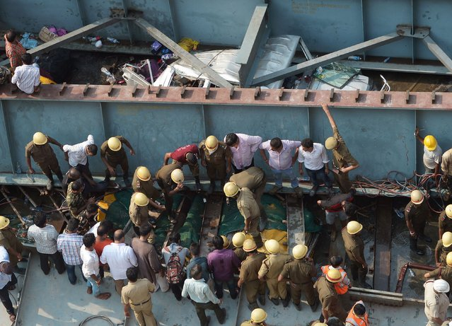 Indian rescue workers and volunteers search for people trapped under the wreckage of a collapsed flyover bridge in Kolkata on March 31, 2016. At least 14 people were killed and dozens more injured when a flyover collapsed in a busy Indian city on March 31, an official said, as emergency workers battled to rescue people trapped under the rubble. (Photo by Dibyangshu Sarkar/AFP Photo)