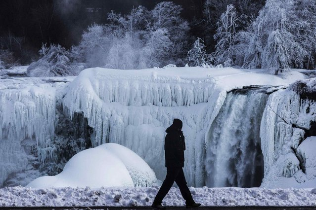 A man walks in front of the partially frozen American side of the Niagara Falls on during sub-freezing temperatures in Niagara Falls, Ontario. (Photo by Mark Blinch/Reuters)