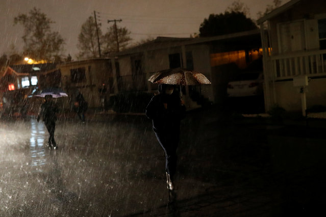 A woman walks in the rain during a flood evacuation at the South Bay Mobile Home Park in San Jose, California U.S., February 21, 2017. (Photo by Stephen Lam/Reuters)