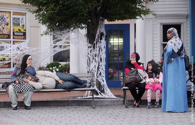 Muslims rest on benches during Great Muslim Adventure Day at Six Flags Great Adventure amusement park