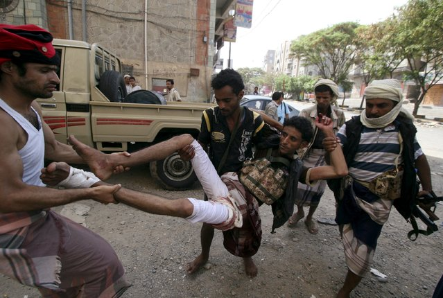Fighters of the Popular Resistance Committees rush a comrade to a hospital after he was injured during clashes with Houthi fighters in Yemen's southwestern city of Taiz May 15, 2015. (Photo by Reuters/Stringer)