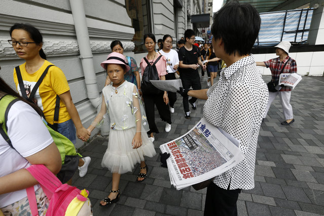 """Hong Kong women distribute newspapers with the headlines """"Millions against Communist China shock the world"""" in a shopping district popular with mainland Chinese tourists in Hong Kong Sunday, July 7, 2019. A march was to go through a popular shopping area for Chinese tourists and end at a high-speed rail station that connects the city to the mainland. (Photo by Andy Wong/AP Photo)"""