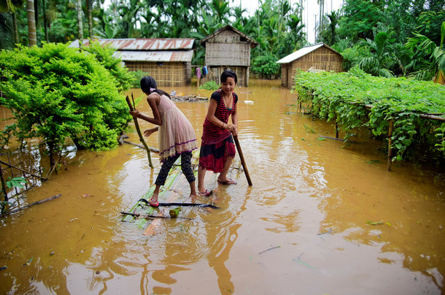 Girls row a makeshift raft past submerged houses at a flood-affected village in Karbi Anglong district, in the northeastern state of Assam, India, July 11, 2019. (Photo by Anuwar Hazarika/Reuters)