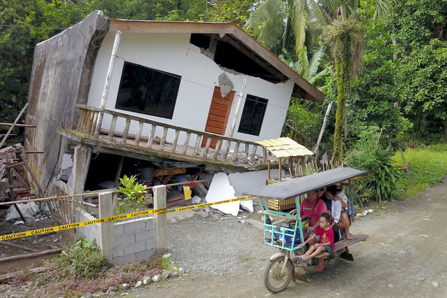 A motorist drives past a destroyed house after a large earthquake that hit Surigao City, in southern island of Mindanao on July 15, 2019. Fifty-one people were injured and several homes, churches and other buildings damaged on Saturday when an earthquake sent terrified residents of the southern Philippines fleeing their homes before dawn, police said. (Photo by Erwin Mascarinas/AFP Photo)