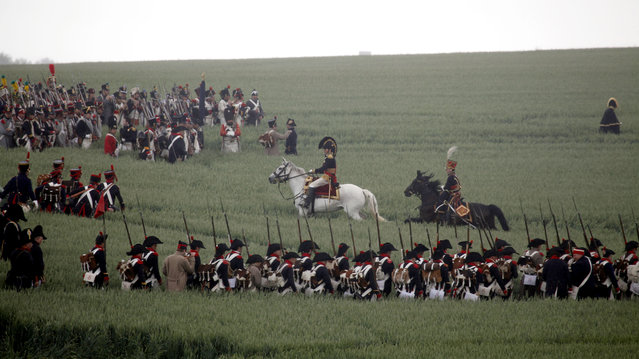 FILE- In this June 20, 2010, file photo, re-enactors march through a field during a living history event of the 1815 Battle of Waterloo in Waterloo, Belgium. More than 5,000 Napoleonic era re-enactors will participate in the upcoming 200th anniversary of the Battle of Waterloo which takes place in June 2015. (AP Photo/Virginia Mayo, File)