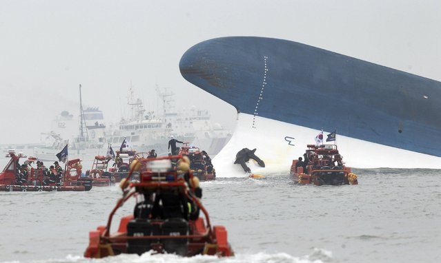 """Part of South Korean passenger ship """"Sewol"""" that has been sinking is seen as South Korean maritime policemen search for passengers in the sea off Jindo April 16, 2014. (Photo by Hyung Min-woo/Reuters/Yonhap)"""