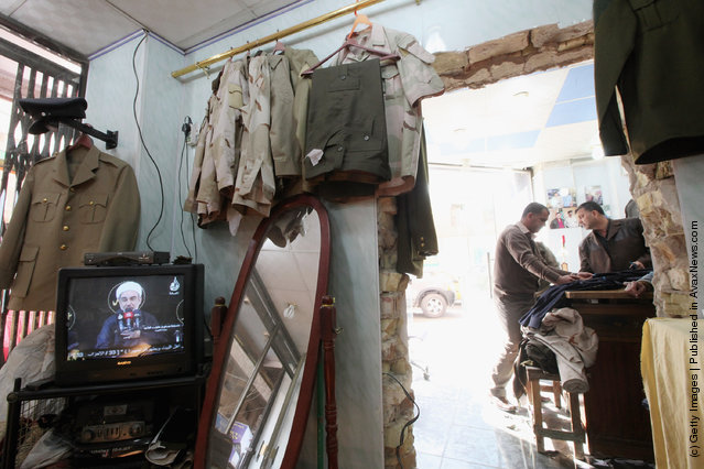 People gather in a shop that sells uniforms to members of Iraq's military and police forces as a religious video plays