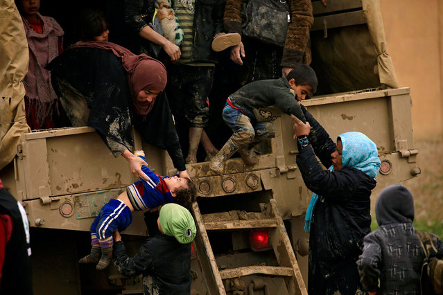 Displaced Iraqi women who fled their homes during a battle between Iraqi forces and Islamic State militants, try to get out of a vehicle with their children at a checkpoint, to be transfer to Hammam al-Alil camp, in Mosul, Iraq, March 20, 2017. (Photo by Thaier Al-Sudani/Reuters)