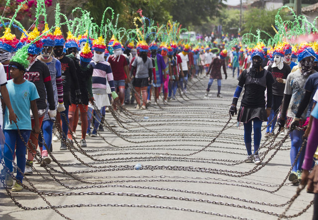 """People dressed as Judas carry chains during the """"Los Encadenados"""" or """"The Chained Ones"""" procession on Good Friday during Holy Week in Masatepe, Nicaragua, Friday, April 18, 2014. (Photo by Esteban Felix/AP Photo)"""