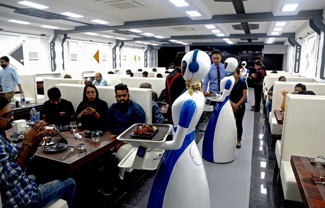 Robots serve trays with food to customers waiting at the Robot theme restaurant in Bangalore, India, 17 August 2019. Six robots are deployed as waiters at the the robot-themed Robot restaurant where each table is equipped with a tablet to place one's order. (Photo by Jagadeesh N.V./EPA/EFE)