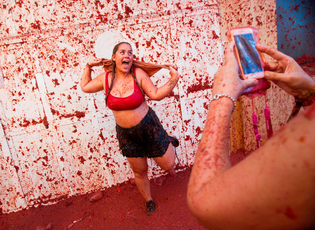 """A reveller covered in tomato pulp poses for a picture during the annual """"Tomatina"""" festival in the eastern town of Bunol, on August 28, 2019. The iconic fiesta, which is billed at """"the world's biggest food fight"""" has become a major draw for foreigners, in particular from Britain, Japan and the United States. (Photo by Jaime Reina/AFP Photo)"""