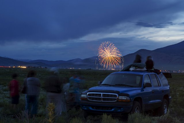 Fireworks explode to celebrate the Fourth of July over the lake at Eagle Nest, New Mexico July 4, 2015. Americans marched in star-spangled parades, ran relay races, gathered for fireworks shows and crowned a new world hot dog eating champion as they celebrated Independence Day in traditional style on Saturday. (Photo by Brian Snyder/Reuters)
