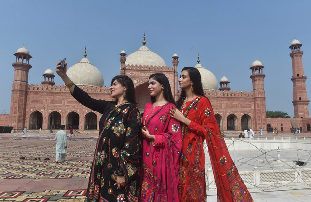 Muslim women take selfie pictures after offering Eid al-Adha prayers at the Badshahi Mosque in Lahore on August 12, 2019. Muslims around the world are celebrating Eid al-Adha (the feast of sacrifice), the second of two Islamic holidays celebrated worldwide marking the end of the annual pilgrimage or Hajj to the Saudi holy city of Mecca. (Photo by Arif Ali/AFP Photo)
