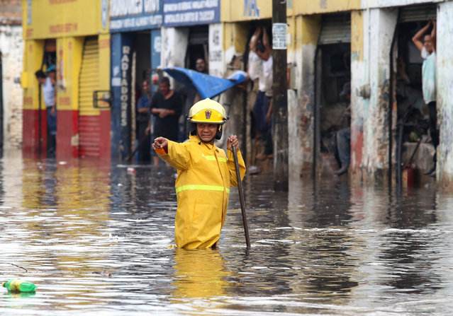 An urban sanitation employee works at a flooded street due to heavy rains, in Guadalajara, 06 July 2015. (Photo by Ulises Ruiz Basurto/EPA)