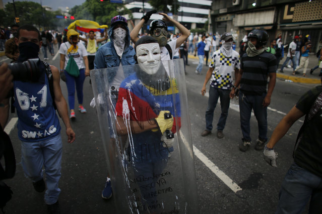 An anti-government protester wearing a mask carries a shield during clashes with security forces in Caracas, Venezuela, Wednesday, April 19, 2017. (Photo by Ariana Cubillos/AP Photo)