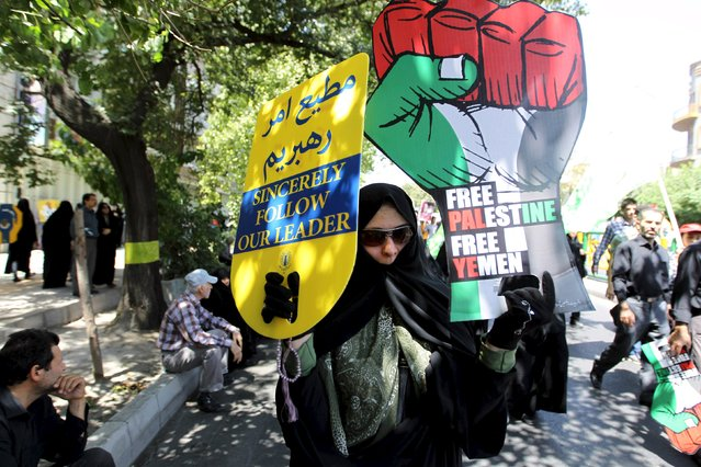 An Iranian woman carries signs during a rally marking al-Quds (Jerusalem) Day in Tehran July 10, 2015. (Photo by Reuters/Stringer/TIMA)