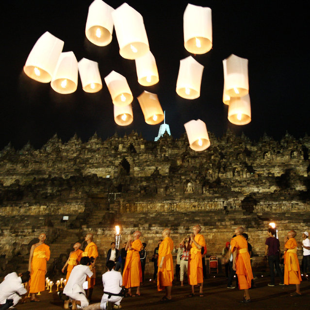 "Buddhist monks release lanterns into the air on Borobudur temple during Vesak Day, commonly known as ""Buddha's birthday"", at the Borobudur Mahayana Buddhist monument on May 28, 2010 in Magelang, Central Java, Indonesia. (Photo by Ulet Ifansasti/Getty Images)"