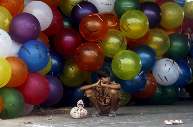 A boy sits next to bunch of balloons for sale on the first day of Eid-al-Fitr which marks the end of the holy fasting month of Ramadan in Karachi, Pakistan July 18, 2015. (Photo by Athar Hussain/Reuters)