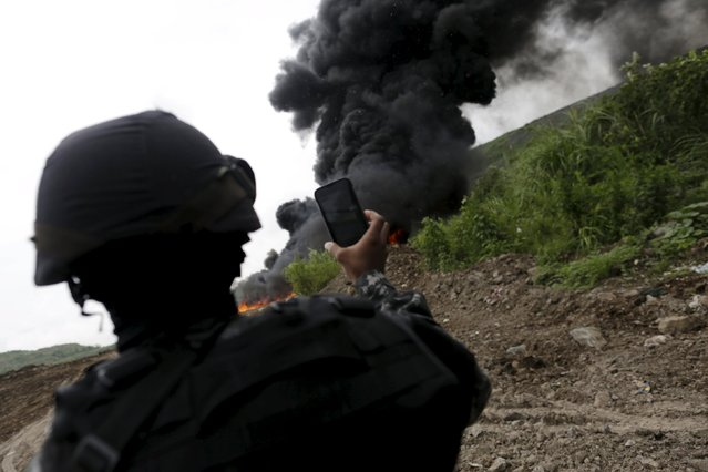 National police officer takes pictures of the smoke during the incineration of illegal drugs in Panama City, July 23, 2015. (Photo by Carlos Jasso/Reuters)