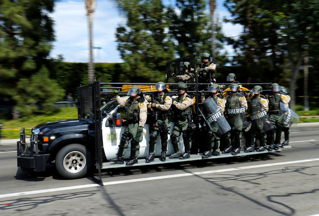 Los Angeles County Sheriffs in riot gear speed down a road  as they chase demonstrators protest near the convention center where U.S. Republican presidential candidate Donald Trump held a campaign rally in Anaheim, California, United States May 25, 2016. (Photo by Mike Blake/Reuters)