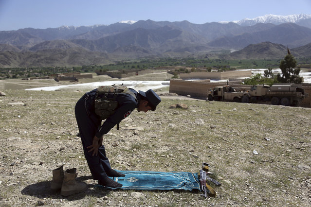An Afghan security personnel prays in Pandola village near the site of a U.S. bombing in the Achin district of Jalalabad, east of Kabul, Afghanistan, Friday, April 14, 2017. U.S. forces in Afghanistan on Thursday struck an Islamic State tunnel complex in eastern Afghanistan with the largest non-nuclear weapon every used in combat by the U.S. military, Pentagon officials said. (Photo by Rahmat Gul/AP Photo)