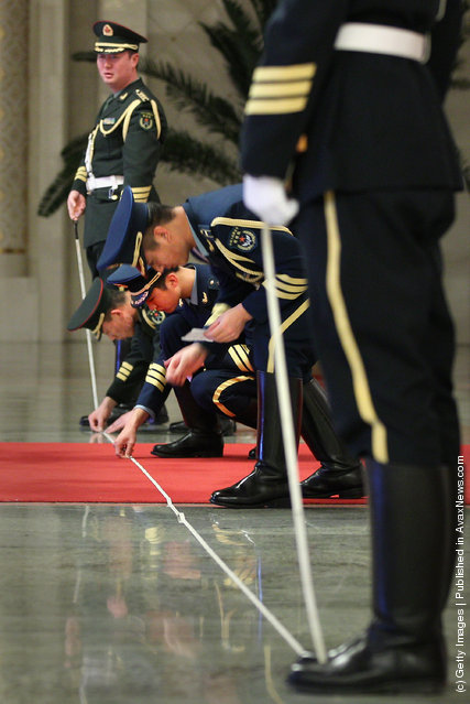 Members of an honour guard use tape measures on the floor to line up as they prepare for a welcoming ceremony for Indonesia's President Susilo Bambang Yudhoyono inside the Great Hall of the People on March 23, 2012 in Beijing, China