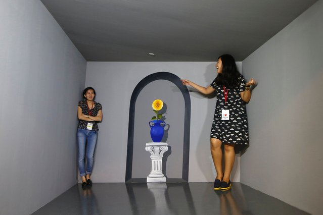 Visitor pose for photos with a 3D installation at a media preview of the Trick Eye Museum at the Resorts World Sentosa in Singapore. (Photo by Edgar Su/Reuters)