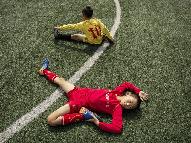 Football players stretch during training at the Evergrande International Football School on June 13, 2014 near Qingyuan in Guangdong Province. (Photo by Kevin Frayer/Getty Images)