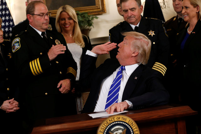 U.S. President Donald Trump reaches back to high-five National Fraternal Order of Police (FOP) President Chuck Canterbury (L) before signing two bills boosting government support for law enforcement first responders, at the White House in Washington, U.S. June 2, 2017. (Photo by Jonathan Ernst/Reuters)