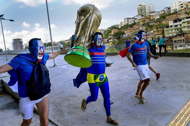 French soccer fans run with a large replica of the World Cup trophy as they arrive to Arena Fonte Nova for their team's World Cup match with Switzerland in Salvador, Brazil. (Photo by Christophe Ena/Associated Press)