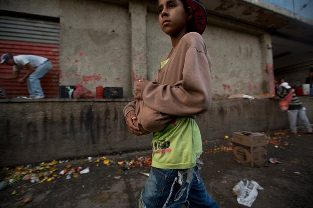 In this June 3, 2016 photo, a boy carries two pineapples he found in the trash area of the Coche public market in Caracas, Venezuela. Staples such as corn flour and cooking oil are subsidized, costing pennies at the strongest of two official exchange rates. But fruit and vegetables have become an unaffordable luxury for many Venezuelan families. (Photo by Fernando Llano/AP Photo)