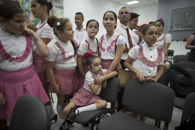 Lizmaria Perez, 7, (C), chats with friends before a rehearsal of the choral group Sol Fa which she is part of before the presentation of the Los Angeles Children's Chorus Young Men's Ensemble, a U.S. children's choir, in Havana, June 15, 2015. (Photo by Alexandre Meneghini/Reuters)