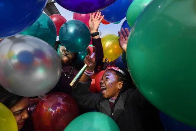 """Essence Merritt, 8, is engulfed by a balloon drop during """"Noon Yards Eve"""", event that gives families the opportunity to celebrate the upcoming new year at an earlier hour, at the Yards Park in Washington, D.C. on December 31, 2019. (Photo by Matt McClain/The Washington Post)"""
