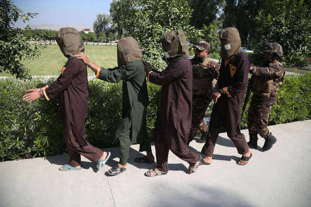 Afghan security officials show a group of suspected militants who are accused of planning attacks on government and security forces after their arrest in Jalalabad, Afghanistan, 15 October 2019. The government now controls less than 60 percent of Afghan territory amid gains for the Taliban, who governed the country for several years prior to the US invasion in October 2001. (Photo by Ghulamullah Habibi/EPA/EFE)