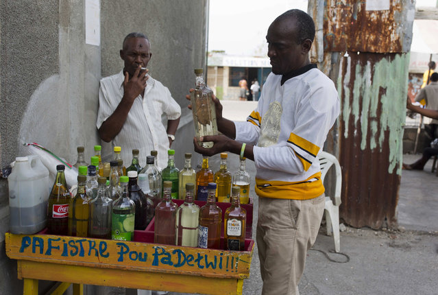 Eddy Lecty shakes a bottle of clairin, a sugar-based alcoholic drink, after adding clove spice to it, as his father Wilfrid Yves Nader smokes nearby and they wait for customers in the Cite Soleil area in Port-au-Prince, Haiti, Tuesday, July 11, 2017. The father-son business has been selling different flavors of clairin at this spot for almost 20 years, which has turned into a meeting place locals coined The Citizens Club. (Photo by Dieu Nalio Chery/AP Photo)