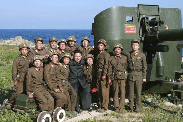 North Korean leader Kim Jong Un poses with soldiers during an inspection of the defence detachment on Ung Islet, which is defending an outpost in the East Sea of Korea, in this undated photo released by North Korea's Korean Central News Agency (KCNA) in Pyongyang July 7, 2014. (Photo by Reuters/KCNA)