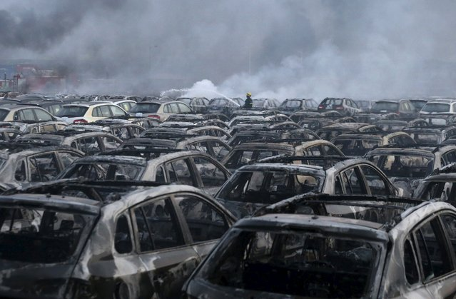 A firefighter works at the site near damaged vehicles as smoke rises from the debris after the explosions at the Binhai new district in Tianjin, China, August 13, 2015. (Photo by Reuters/China Daily)