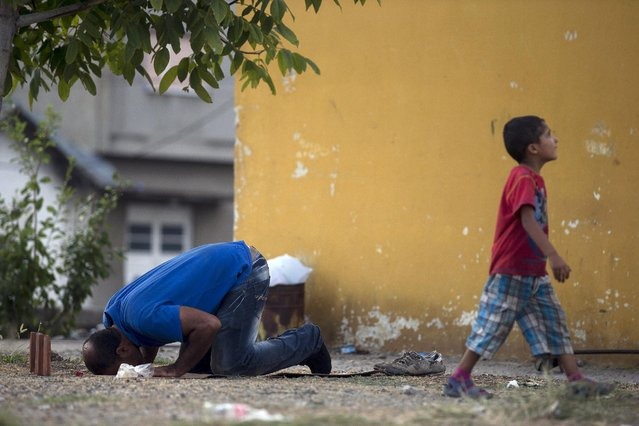 A migrant man prays next to a child at Gevgelija train station in Macedonia, close to the border with Greece, August 14, 2015. (Photo by Stoyan Nenov/Reuters)