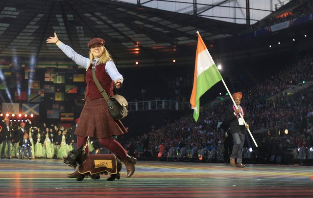 A host with a Scottish Terrier walks ahead of India's flag bearer Vijay Kumar, right, during the opening ceremony for the Commonwealth Games 2014 in Glasgow, Scotland, Wednesday July 23, 2014. (Photo by Frank Augstein/AP Photo)