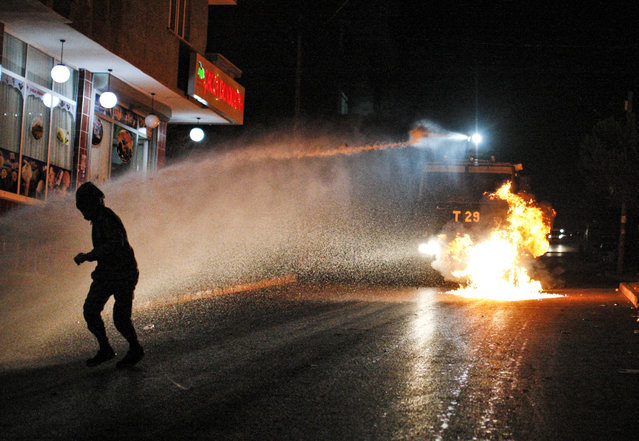A left-wing protester runs to avoid water from a Turkish police water canon, after he threw a petrol bomb at it, during minor clashes between police and people protesting Turkey's operations against Kurdish militants. in Istanbul, early Sunday, August 16, 2015. There had been a sharp escalation of violence lately between Turkey's security forces and the Kurdistan Workers' Party, or PKK. and the collapse of a two-year peace process with the rebels. Dozens of people, mostly Turkish soldiers, have died since July in the renewed violence. (Photo by Cagdas Erdogan/AP Photo)