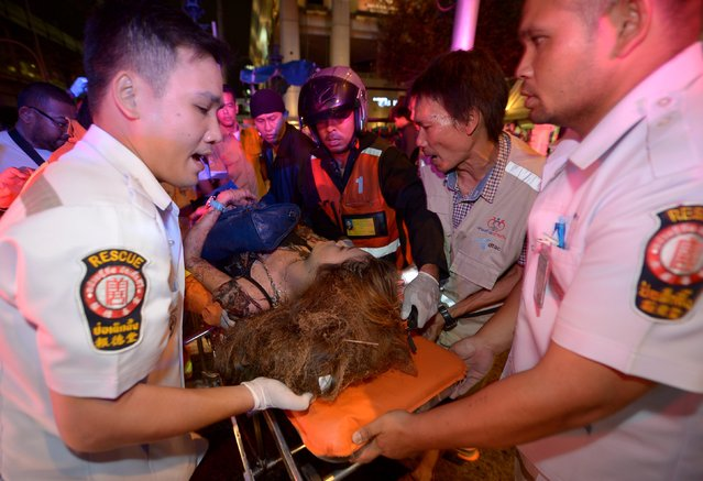 Thai rescue workers transport an injured person after a bomb exploded outside a religious shrine in central Bangkok late on August 17, 2015 killing at least 10 people and wounding scores more. (Photo by Pornchai Kittiwongsakul/AFP Photo)
