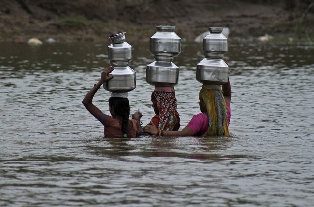Indian women hold each other as they cross the River Heran after collecting drinking water near Sajanpura village in Chhota Udepur district of Gujarat state, India, Tuesday, August 5, 2014. Dozens of women from the Sajanpura village cross the river every day to collect drinking water from the other side since the water in their village is saline and muddy. (Photo by Ajit Solanki/AP Photo)