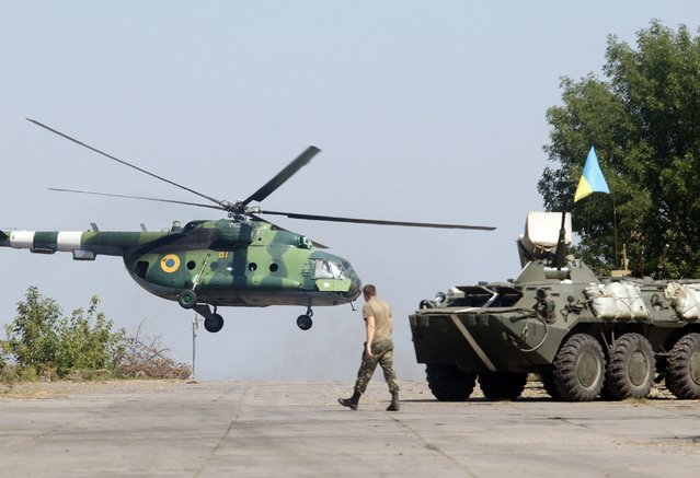 A serviceman walks near an APC while a helicopter flies  on the position of the Ukrainian troops in Donetsk region on August 9, 2014. Fighting with pro-Russian separatists in eastern Ukraine has left 13 troops dead in the last 24 hours, Ukraine's military said Saturday. (Photo by Anatolii Stepanov/AFP Photo)
