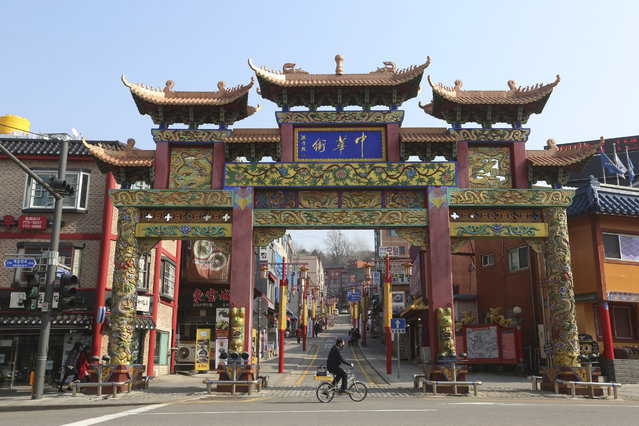 In this February 14, 2020. photo, a man wearing a face mask rides a bicycle to pass the Chinatown's main entrance gate in Incheon, South Korea. Even as cases and deaths from the new virus mount, fear is advancing like a tsunami – and not just in the areas surrounding the Chinese city of Wuhan, the center of the outbreak that has been declared a global health emergency. A restaurant owner in the Chinatown says visitors have dropped by 90%. (Photo by Ahn Young-joon/AP Photo)